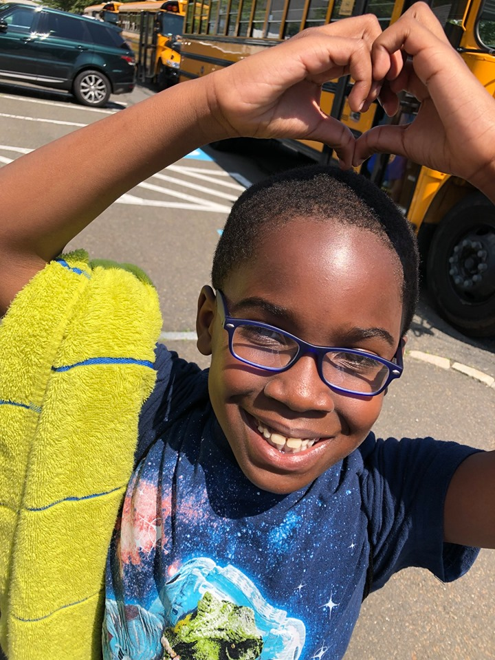 Young boy wearing glasses in front of a school bus