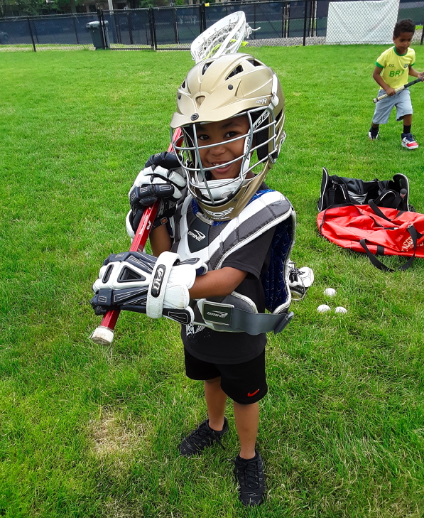 Smiling child wearing lacrosse gear